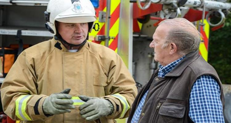 Firefighter talking to a man