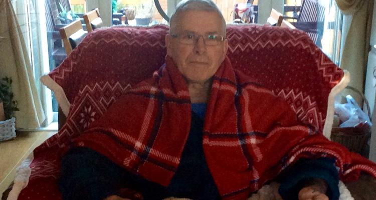 Man keeping warm at home by wrapping himself in blankets