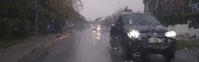 Car on a road in wind and rain