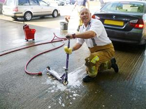 Firefighter washing a child's scooter