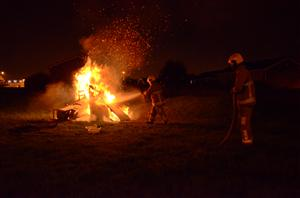 Firefighters extinguish an unattended bonfire
