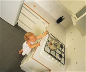Child trying to grab a pan on a stove