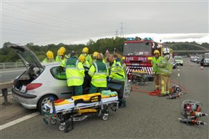 Firefighters and paramedics work together to release casualties from vehicle
