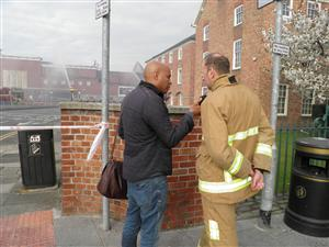 Local media interviewing a firefighter at the scene of a major fire in Warrington
