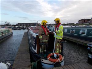 Firefighters on a narrow boat, after tackling a fire involving a log burner on the boat