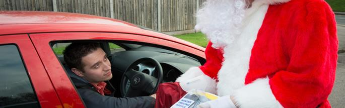 Santa offering road safety tips to a motorist in a car