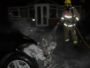 Firefighters fighting the car fire