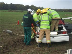 Crew and paramedic removing casualty from car
