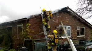 Firefighters damping down the roof