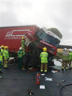 Firefighters at the scene of a road traffic collision involving large vehicle on M62