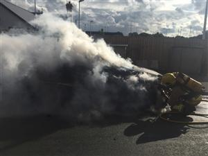 Smoke coming from car fire being extinguished by firefigters