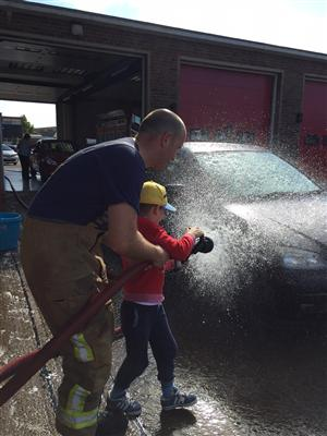 Firefighter washing a car with a young boy