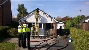 Firefighters and police at the scene of a fire in Poynton