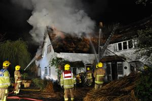 Firefighters tackling a thatched roof fire
