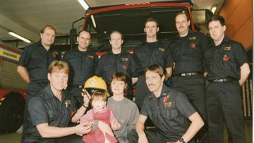 Jade Broderick and her mum Julie Lloyd on a visit to Warrington Fire Station eight months after the fire in 1995, pictured with firefighters, from left, back row, John Mather, Alan Griffiths, Andy Hinde, Dave Norris and Damon Leonard; front row, Gus O'Rourke and Martin Dowle (picture courtesy of Warrington Guardian)