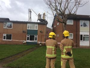 Firefighters staning outside a block of flats, following a roof fire