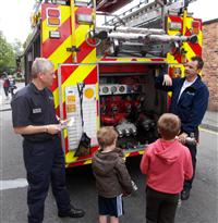 Firefighters show the fire engine to local kids