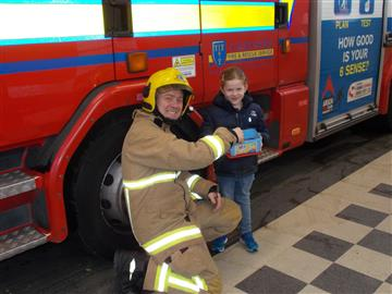 Elena visited Wilmslow Fire Station with a cake for firefighters