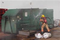 A high pressure lance is used to bring a rubbish compactor fire under control