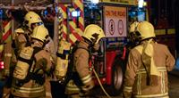 Firefighters in breathing apparatus and a fire engine