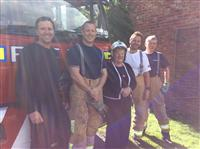 Wilmslow crews pose with grateful resident after extinguishing skip fire at her home