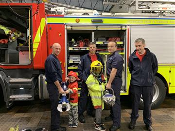 Sam and Dylan Francis enjoy holding firefighter equipment during their special visit to Widnes Fire Station. They are pictured with firefighters, from left, Darren Wright, Sam Molyneaux, Matty Thornberry and Ruari Lennon.