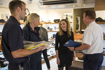 fire safety discussion between a local shop manager and members of Cheshire Fire and Rescue Service