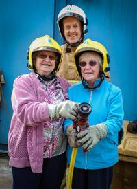 Two women with a firefighter