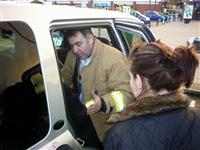 Firefighter checks that a childs car seat is fitted correctly