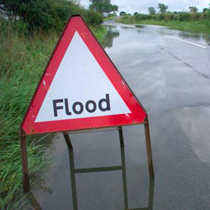 A flooded road with a flood sign