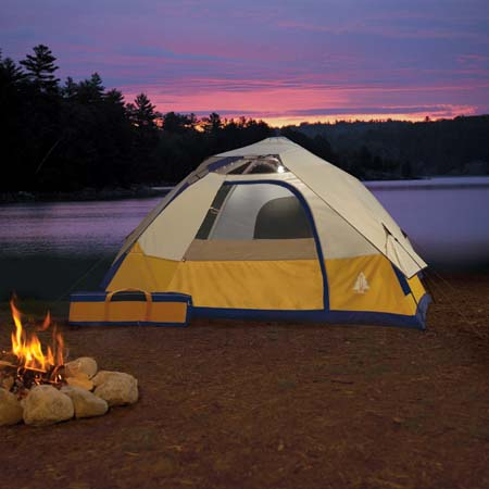 A tent on a campsite with a campfire burning close to the tent