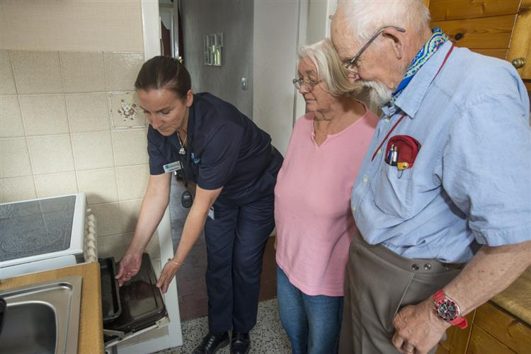 Member of the fire service talking fire safety to older residents
